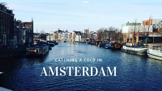 "A picture of one of Amsterdam's Canals with the title of the blog post overlaying it: ""Catching a cold in Amsterda."""