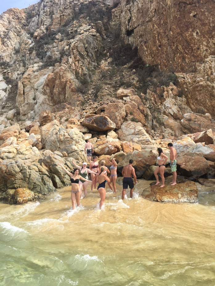 Bri and her friends/family posing in the water of a cove near Cabo San Lucas.