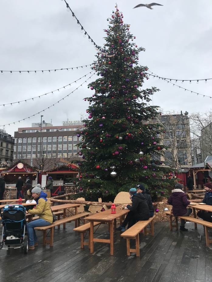 Tall Christmas tree decorated with colorful ornaments, stood in the center of a Christmas market in Zurich.