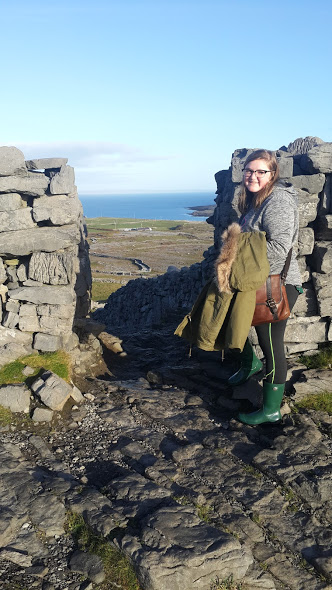 Bri standing at the entrance of fort Angus on the Island of Inishmore. The rolling green landscape in the background.