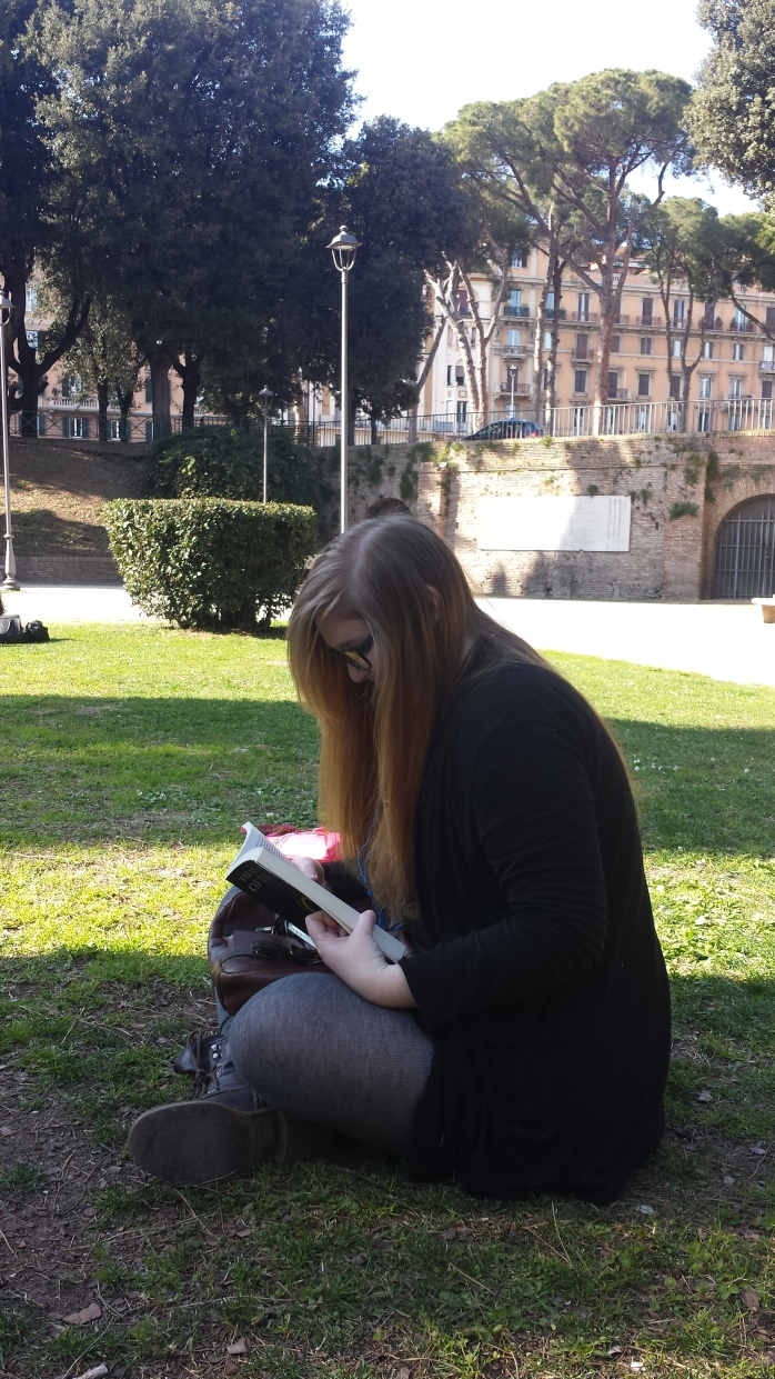 A Picture of Bri sitting in the Park behind the Castel Sant'Angelo. She is looking down at the book, with her legs crossed infront of her.