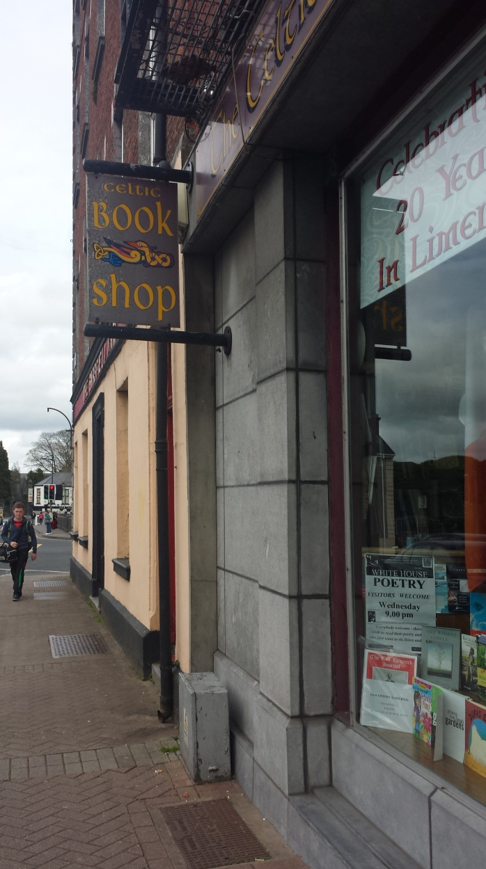 Photo of a Celtic Book Shop sign. The letters are in the Celtic swirl font, the color yellow on a grey back drop.