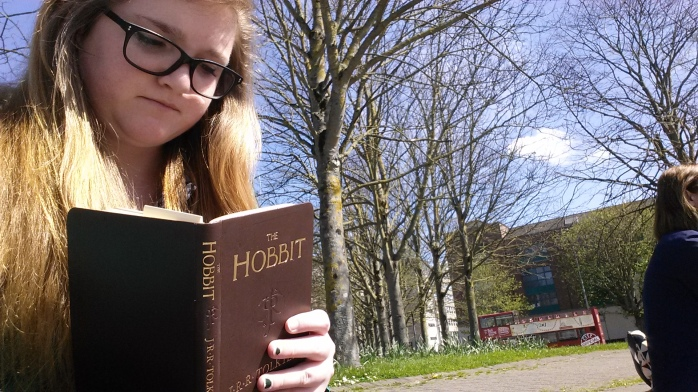 Bri taking a selfie of herself readin her pocket edition of the Hobbit. She is holding the book so that when she looks down at the page she has a double chin and a frown, like an idiot.