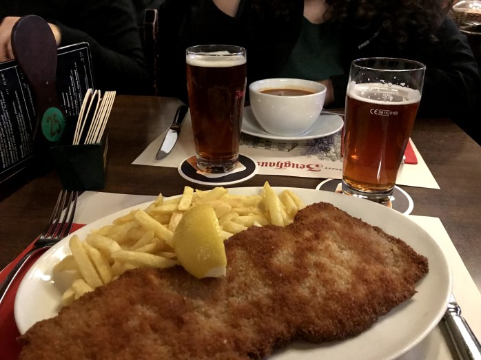 A Picture of a large plate of shnitzel, fries, and a lemon wedge on top. There are also two beers in the shot.