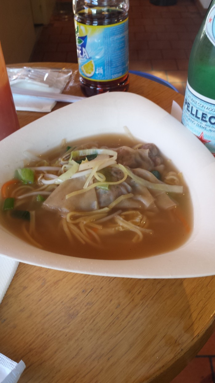A picture of a bowl of wonton soup, with soft drinks in the background.