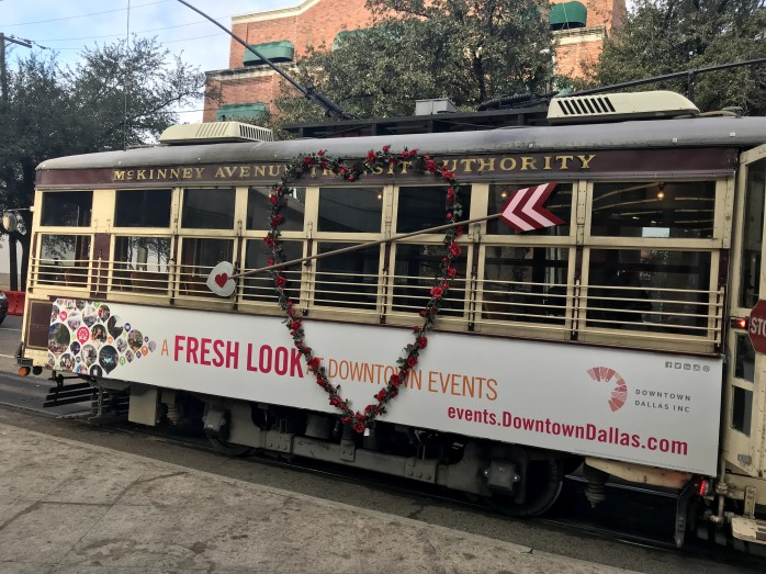 A picture of a brown trolley with a flower shaped wreath with an arrow cutting through it. The trolley is decorated for Valentine's Day.