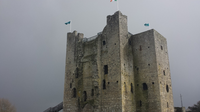 A square stone fortress. There are three flags on top of the castle.
