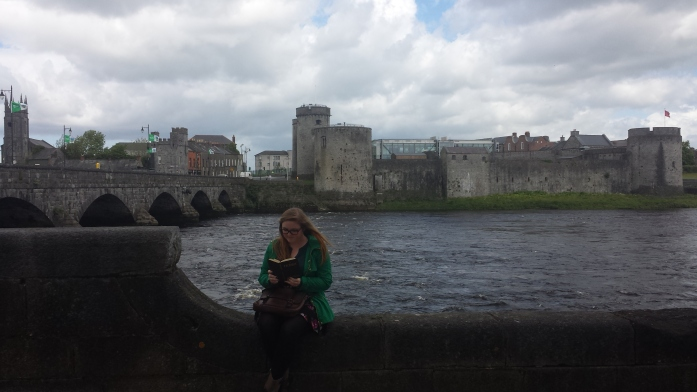 picture of King John's CAstle from the opposite side of the Shannon River. Bri sits on the ledge looking down at a book with the castle in the distance. The castle is more like stone walls with various towers.