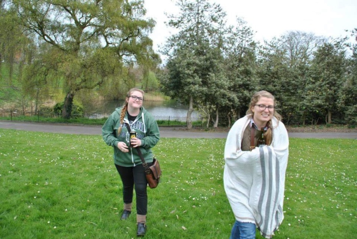 Bri and her friend chelsea walking in Phoenix park, with one of the ponds in the background.