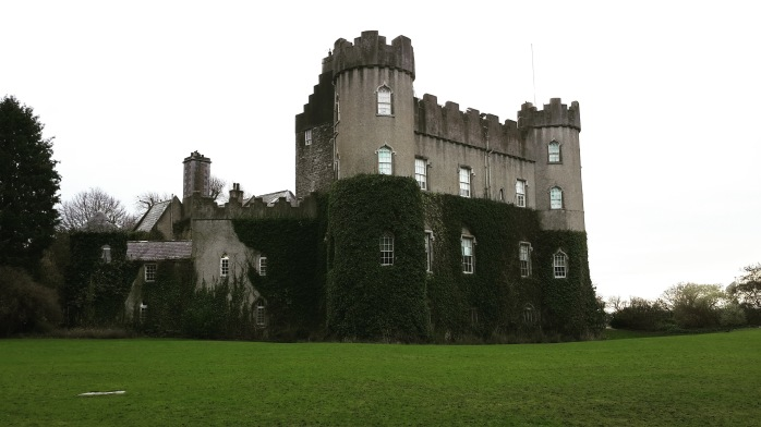 pictured is Malahide CAstle with moss covering the bottom house of the grey manor. It looks like a square Disney Castle