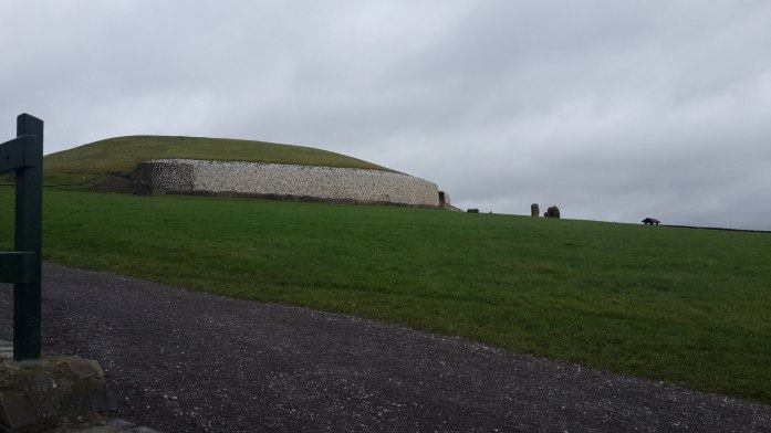 The Tomb of newgrange viewed from the bottom of the hill it was built on. It is a cloudy day, and the grass is particularly green against the contrast of the white stone of Newgrange.